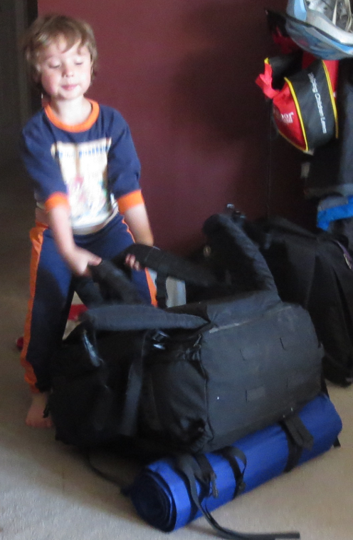 Ian trying to lift Philip's backpack.